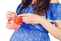 Gestrickte Babyschuhe der schwangeren Frau weibliche Holding Lizenzfreie Stockfotos