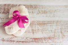 Gestrickte Babysocken mit rosa Bogen auf der Holzoberfläche Lizenzfreie Stockfotos