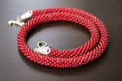 Gestrickte Halskette von den großen roten Perlen Stockfotos