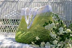 Gestrickte handgemachte grün-weiße Tasche bleibt auf weißer Weidencouch im Garten mit blühendem spirea bouqet beiseite lizenzfreie stockfotos