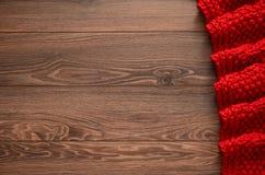 Gestrickte rötliche Decke auf einem hölzernen Hintergrund mit Kopienraum Stockfoto