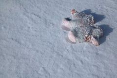 Gestrickte rote oder rosa Babyhandschuhe, die auf dem weißen Schnee liegen Stockbild