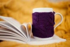 Gestrickte Schale mit offenem Buch Stockfoto