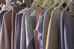 Gestrickte selbst gemachte Kleidung von den verschiedenen Farben, die im stor hängen Lizenzfreie Stockfotos
