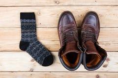 Gestrickte Socken und Lederstiefel auf hölzernem Hintergrund Stockbilder