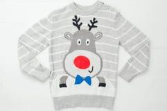 Gestrickte Strickjacke mit lustigen Weihnachtsrotwild auf hölzernem weißem Hintergrund Hässliche Strickjacke stockfotos