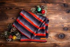 Gestrickter Schal in den schwarzen und roten Streifen und in den Weihnachtsdekorationen auf hölzernem Hintergrund stockfotografie
