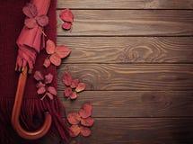 Gestrickter Schal von Burgunder-Farbe mit Herbstlaub und einem umbrel stockfotos