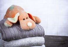 Gestrickter Spielzeughund auf dem Stapel der gestrickten Kleidung auf Holztisch Lizenzfreie Stockfotos