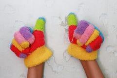 Gestricktes children& x27; s-Handschuh mit bunten Streifen und okayzeichen Lizenzfreie Stockfotografie