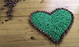 Gestricktes grünes Herz auf hölzernem Hintergrund Stockfotografie