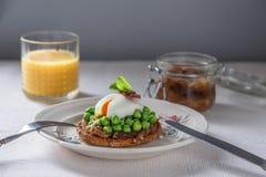 Gestroopte Ei en Erwten op volkorenmeel geroosterd brood Jus d'orange en uijam op achtergrond stock foto's