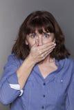 Gestörte attraktive reife Frau, die ihren Mund versteckt Stockfotos