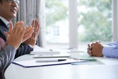 Gesture of congrats. Pen with document and hands of young men on desk and ovations of two mature employers after interview or report royalty free stock photos