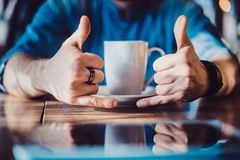 A gesture with the fingers of a shaka. With a cup of coffee stock photo