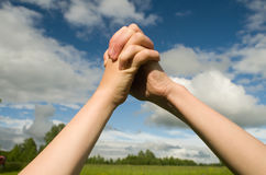 A gesture of friendship between the two hands. Two teenagers linked hands in triangle shape on the background of the summer sky Royalty Free Stock Images