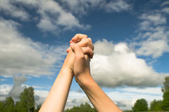 A gesture of friendship between the two hands. Two teenagers linked hands in triangle shape on the background of the summer sky Stock Photography