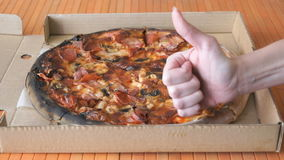 A gesture of a hand, showing fingers up over pizza