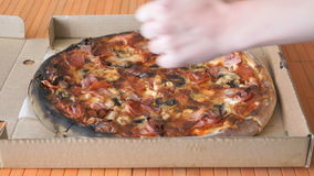 A gesture of a hand, showing fingers up over pizza stock footage