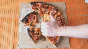 A gesture of a hand, showing fingers up over pizza stock video footage