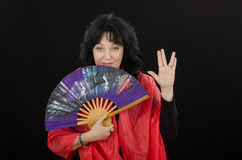 Gesture long life and prosperity shown by geisha. White mature actress shows long life and prosperity gesture on black background stock photography