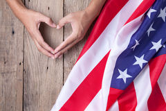 Gesture made by hands showing symbol of heart with american flag. On old wooden background Royalty Free Stock Image