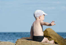 Gesture not to bother. Little boy in swimming trunks sits on the seashore, place for text.  Stock Images