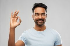 Happy indian man in t-shirt showing ok hand sign royalty free stock photo