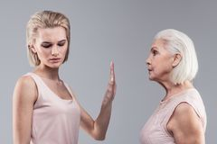 Categorical blonde woman shutting her mother up. Gesture of silence. Categorical blonde women shutting her mother up while resolutely raising hand royalty free stock image