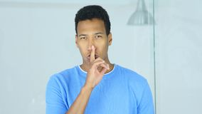 Gesture of Silence by Young Afro-American Man, Finger on Lips stock photo