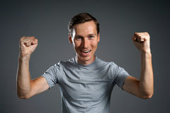 Gesture of success. Smiling man in gray t-shirt with raised hands. Royalty Free Stock Images