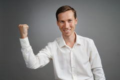 Gesture of success. Smiling man in white shirt with raised hand. Stock Photo