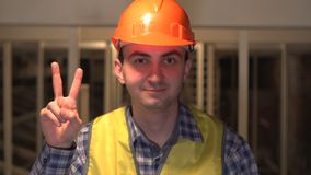 Gesture of success, victory sign by worker or an engineer or architect on construction site. Concept: construction, worker, engineering, design Victory stock footage