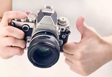 Gesture thumbs up and retro SLR camera isolated Royalty Free Stock Photos