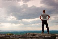 Gesture of triumph. Happy hiker in greyshirt and dark trousars. Tall man on the peak of sandstone cliff watching down to landscape Royalty Free Stock Image