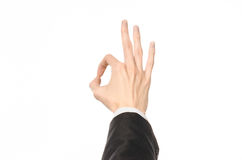 Gestures and Business theme: businessman shows hand gestures with a first-person in a black suit on a white background isolated Royalty Free Stock Photo