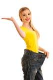 Gesturing επιτυχία γυναικών δεδομένου ότι έχασε το βάρος φορώντας πάρα πολύ μεγάλο trous Στοκ Εικόνες