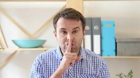 Gesturing del silenzio dall'uomo che si siede nell'ufficio Immagini Stock
