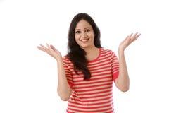 Gesturing felice della giovane donna mani aperte contro bianco Immagine Stock