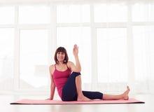 Gesturing femminile sportivo positivo mentre avendo resto su una stuoia di yoga Fotografie Stock