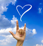 Gesturing hand on blue sky. Royalty Free Stock Photo