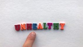 Gesund farbige hölzerne Buchstaben auf einem weißen Blatt Papier stock video footage