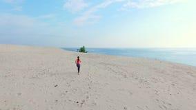 Gesund, läuft Jungesportschönheit in der Sonnenbrille entlang den Sand, auf dem Strand, im Sommer, in Richtung zur Sonne, an stock footage