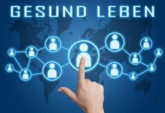 Gesund leben text concept. Gesund leben - german word for healthy living - text concept with hand pressing social icons on blue world map background Stock Photos