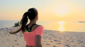 Gesund, tragen Junge Schönheitsläufe entlang dem Sand, auf dem Strand, im Sommer, in Richtung zur Sonne, bei dem Sonnenaufgang zu stock footage