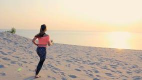 Gesund, tragen Junge Schönheitsläufe entlang dem Sand, auf dem Strand, im Sommer, in Richtung zur Sonne, bei dem Sonnenaufgang zu stock video footage