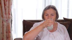Gesunde ältere Dame, die ein Glas frische Milch trinkt stock video