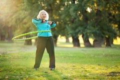 Gesunde ältere Frau, die Übungen in der Natur tut Stockfotografie