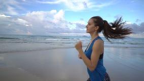 Gesunde aktive Frau in der blauen Spitze, die auf dem Strand nahe Meer auf Sonnenuntergang läuft stock video footage