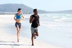 Gesunde aktive Paare, die durch Wasser auf dem Strand laufen Stockbild